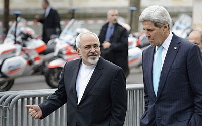 US Secretary of State John Kerry (right), speaks with Iranian Foreign Minister Mohammad Javad Zarif as they walk in Geneva, Switzerland, ahead of nuclear discussions, January 14, 2015. (AP/Keystone, Laurent Gillieron, File)
