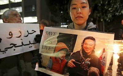 In this Friday, Jan. 30, 2015 file photo, a protester holding a photo of Japanese journalist Kenji Goto, who was taken hostage by the Islamic State group, appeals to the government to save Goto during a rally in front of the prime minister's official residence in Tokyo. (AP Photo/Koji Sasahara, File)