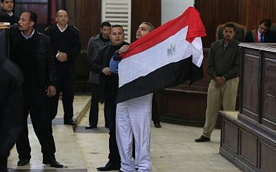 Canadian al-Jazeera English journalist Mohamed Fahmy holds up an Egyptian flag after a retrial in a courthouse near Tora Prison in Cairo, Egypt, February 12, 2015. (photo credit: AP/Hassan Ammar)
