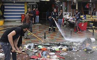 Municipality workers help clean up the site of a suicide bombing that targeted a street filled with hardware stores, killing over 20 people and wounding at least 45, Baghdad, Iraq, February. 7, 2015. (photo credit: AP/Karim Kadim)