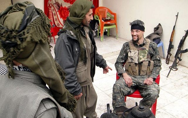 In this Thursday, Jan. 29, 2015 photo, Jordan Matson, 28, right, a former U.S. Army soldier, takes a break with other fighters from the main Kurdish militia, the People's Protection Units, or YPG, in Sinjar, Iraq. (Photo credit: AP/Vivian Salama)