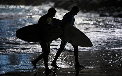 Israeli surfers walk out of the water after competing in a night surfing competition in the Mediterranean sea in Ashdod, southern Israel, Wednesday, Feb. 4, 2015 (AP Photo/Oded Balilty)