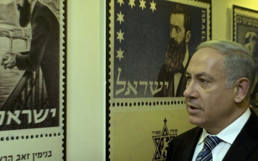 In this April 18, 2010 file photo, Prime Minister Benjamin Netanyahu looks at posters of stamps carrying the portrait of Theodor Herzl, the founder of modern Zionism, in Jerusalem. (Photo credit: AP/Sebastian Scheiner)