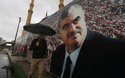 A Lebanese man walks by a giant poster of slain former Lebanese Prime Minister Rafik Hariri, that was put up near his grave, in preparation to mark the 10th anniversary of his assassination, in downtown Beirut, Lebanon, Wednesday, Feb. 11, 2015. (AP Photo/Hussein Malla)