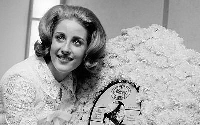 In this May 5, 1964, file photo, singer Lesley Gore hugs a flowered record at her 18th birthday party celebrated at the Delmonico Hotel in New York. (Photo credit: AP/Marty Lederhandler, File)