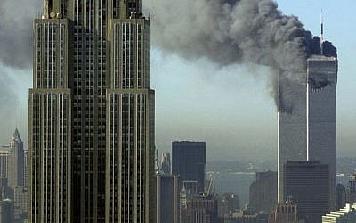In this Tuesday, Sept. 11, 2001 file photo, plumes of smoke rise from the World Trade Center buildings in New York. The Empire State building is seen in the foreground. (photo credit: AP Photo/Patrick Sison, File)