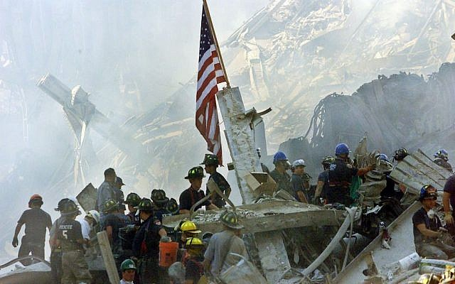 In this Sept. 13, 2001 file photo, an American flag flies over the rubble of the collapsed World Trade Center buildings in New York. (photo credit: AP Photo/Beth A. Keiser, File)