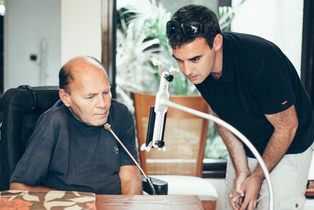 Sorin Hershko, who was injured in the raid on Entebbe in 1976, using the Sesame phone with Sesame Enable CEO Oded Ben Dov. (Basti Hansen/JTA)