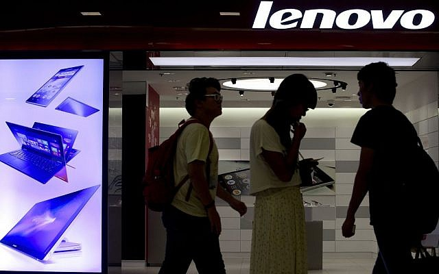 In this Aug. 15, 2013 file photo, people walk past a Lenovo flagship experience store in Beijing, China. (photo credit: AP/Andy Wong, File)