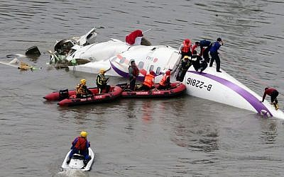 Emergency personnel approach a commercial plane after it crashed in Taipei, Taiwan, Wednesday, Feb. 4, 2015. (photo credit: AP Photo)