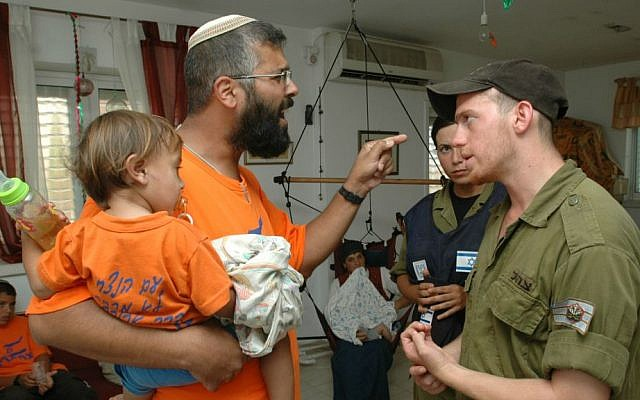 A settler in Netzarim argues with soldiers who have come to evacuate him from his home during the Disengagement from Gaza, August 22, 2005. (Flash90)
