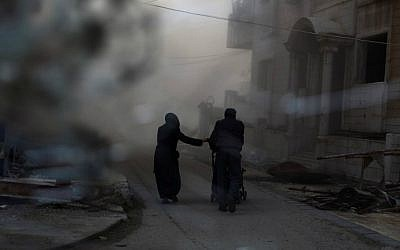 A picture taken from behind broken glass shows a couple pushing a baby stroller as they rush to check their house following an air strike on the rebel-held Damascus suburb of Douma, on February 21, 2015. (screen capture: AFP/Abd Doumany)