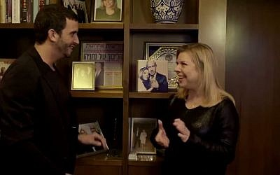 Sara Netanyahu and TV celebrity interior designer Moshik Galamin talk in the prime minister's residence, Jerusalem. On the shelf is a picture of the Netanyahu's, gifted to them by Galamin. (YouTube: screenshot)
