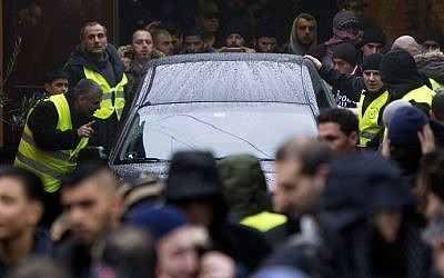 Mourners surround the hearse with late Omar Abdel Hamid El-Hussein leaving the Mosque on Dortheavej in Copenhagen driving to the Muslim cemetery in Broendby south of Copenhagen on February 20 2015. (photo credit: AFP/Scanpix Denmark/Nils Meilvang)