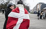 A woman and a man wearing the danish flag stand outside the main Synagogue in Copenhagen on February 15, 2015 following two fatal attacks in the Danish capital, a month after the Paris attacks. (photo credit: AFP/Claus Bjorn Larsen)