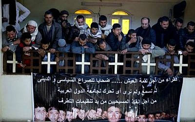 Villagers mourns over Egyptian Coptic Christians who were captured in Libya and killed by extremists affiliated with the Islamic State group, inside the Virgin Mary Church in the village of el-Aour, near Minya, 220 kilometers (135 miles) south of Cairo, Egypt, Monday, February 16, 2015 (photo credit: AP/Hassan Ammar)