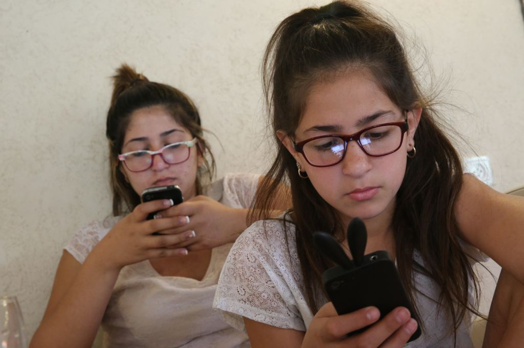 Sisters on their phones (photo credit: Nati Shochat/Flash 90)