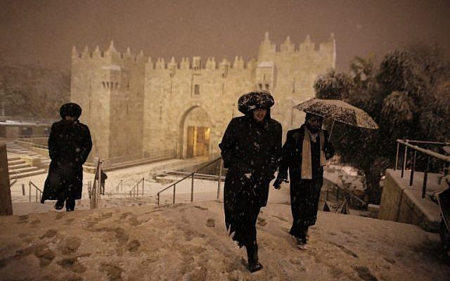 Ultra-Orthodox Jewish men walk near Damascus Gate in Jerusalem's Old City as snow falls on February 19, 2015. (AFP/Ahmad Gharabli)