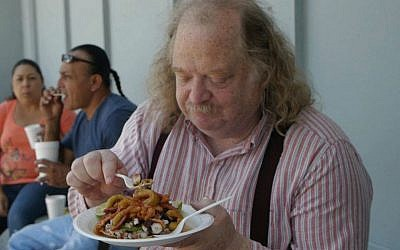 Jonathan Gold shown in 'City of Gold' digging into a Poseidon Tostada from the Mariscos Jalisco taco truck in Los Angeles. (JTA)