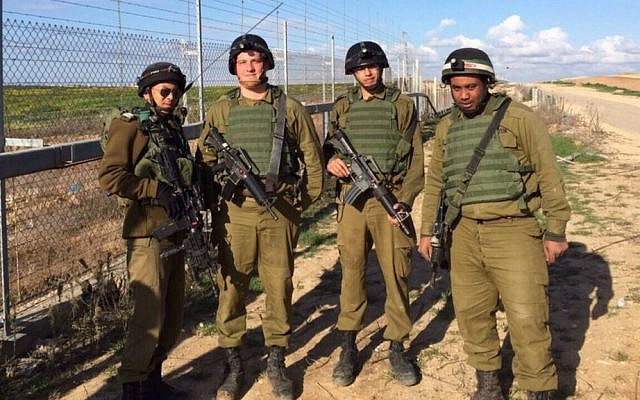 Deputy unit commander, Sgt. First Class Reuven Tautang, left, and three Kometz soldiers along the fence (photo credit: IDF Spokesperson's Unit)