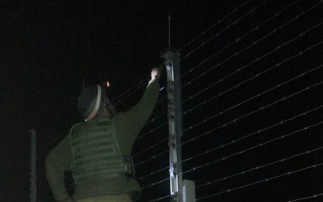 A Kometz soldier, standing on a ladder on the Gaza side of the barrier, fixing the fence (photo credit: Netta Asner/IDF Spokesperson's Unit)