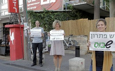 Shabus organizers stand outside Jerusalem's Lev Smadar Theater, a secular Jerusalemite hangout on Saturdays, holding signs that read, 'There is a solution, Shabus' (photo credit: Courtesy Shabus)