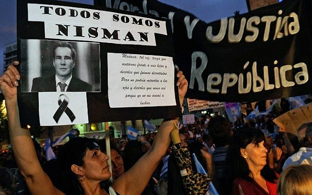 """A woman holds a signs with prosecutor Alberto Nisman's portrait in Rosario, Argentina on February 18, 2015, during a march simultaneous to the """"Marcha del silencio"""" (March of Silence) called by Argentine prosecutors in memory of their late colleague Nisman in Buenos Aires. (photo credit: AFP/NA - Agencia Cordoba)"""