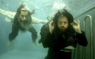 "This undated photo provided by Channel 8 and Go2Films shows Ori Gruder, left, and rabbi Yisrael Aharon Itzkovitz swimming in their clothes in a ritual bath, which is created for publicity purpose for ""Sacred Sperm,"" a film Gruder directed. (photo credit: AP Photo/Gliad Kavalerchik)"