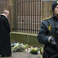 The Dean of Copenhagen Cathedral Anders Gadegaard (second from the right) and his congregation offer prayers for the shooting victims outside the synagogue Krystalgade in Copenhagen, on February 15, 2015 after two fatal attacks in the Danish capital, at a cultural center during a debate on Islam and free speech and a second outside the city's main synagogue. (AFP/Odd Andersen)
