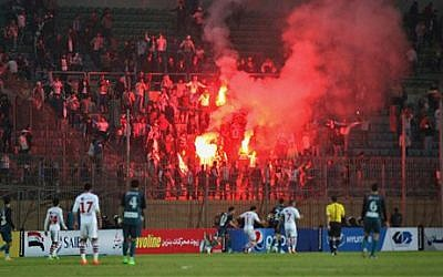 Soccer fans hold lit flares at the stand as they watch a match between Egyptian Premier League clubs Zamalek and ENPPI at Air Defense Stadium in a suburb east of Cairo, Egypt, Sunday, February 8, 2015 (photo credit: AP/Ahmed Abd El-Gwad, El Shorouk newspaper)