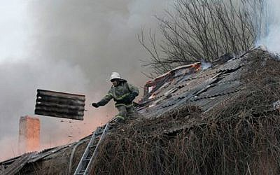 A firefighter dismantles a roof to extinguish a building on fire after shelling between Russian-backed separatists and the Ukrainian government in Artemivsk, Ukraine, February 14, 2015. (photo credit: AP/Petr David Josek)