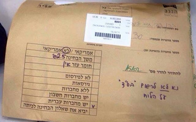 """An envelope containing exams, on top of which were written orders not to write BS""""D on the classroom board. (photo credit: Facebook screen capture)"""