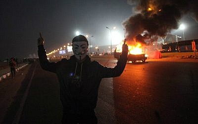 An Egyptian man wearing a mask of the anonymous movement gestures near a burning car outside a sports stadium in a Cairo's northeast district, on February 8, 2015 during clashes between supporters of Zamalek football club and security forces. (photo credit: AFP/STR)