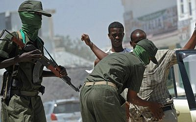 Somalia federal government soldiers conduct a random check of public transport vehicles during a patrol on the streets of Mogadishu on February 18, 2015, as part of an operation against al-Shabab insurgents (photo credit: AFP/Mohamed Abdiwahab)
