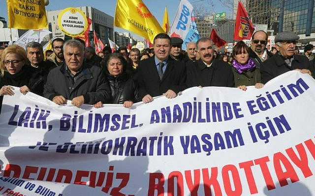 "Members of the Turkish education unions hold a banner that reads, ""No to obligatory religious education"", as they protest against the government's education policies in Ankara on February 13, 2015. (photo credit:  AFP/Adem Atlan)"