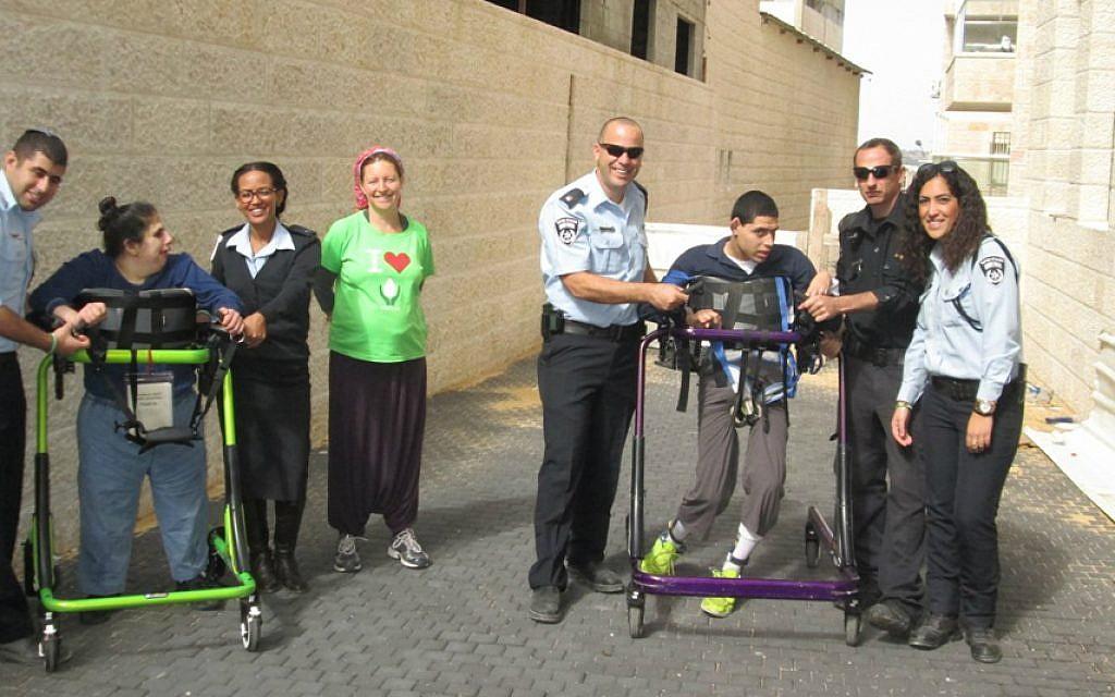 Police officers from Jerusalem's Lev Habira station  and ALEH residents take a break from their training for the Jerusalem Marathon. (courtesy of ALEH Jerusalem)