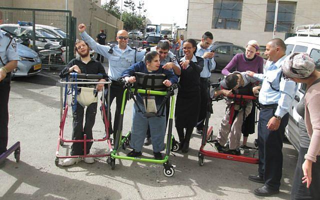 Israeli police officers from Jerusalem's Lev Habira station help residents of ALEH train to 'run' the Jerusalem Marathon in their walkers. (Courtesy of ALEH Jerusalem)