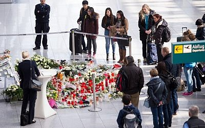 People pay their respects at a memorial with messages, candles and flowers for the victims of the Germanwings plane crash in the French Alps can be seen at the airport in Duesseldorf on March 28, 2015.  (photo credit: AFP/DPA/MARIUS BECKER)