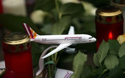 A toy airplane of German airline Germanwings placed among candles and flowers at the airline's headquarter in Cologne, western Germany, on March 27, 2015. (phot credit: AFP/ DPA/OLIVER BERG)