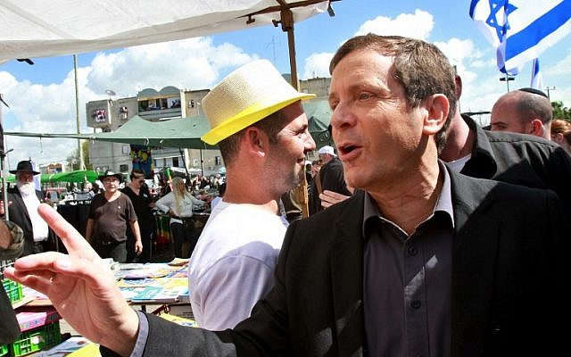 Isaac Herzog visits an open market during an election campaign rally in the city of Lod on March 3, 2015. (photo credit: AFP/GIL COHEN-MAGEN)