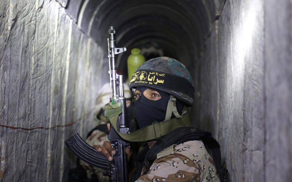 Palestinian terrorists from the Islamic Jihad's armed wing, the Al-Quds Brigades, squat in a tunnel, used for ferrying rockets and mortars back and forth in preparation for the next conflict with Israel, as they take part in military training in the south of the Gaza Strip, on March 3, 2015. (AFP/Mahmud Hams)