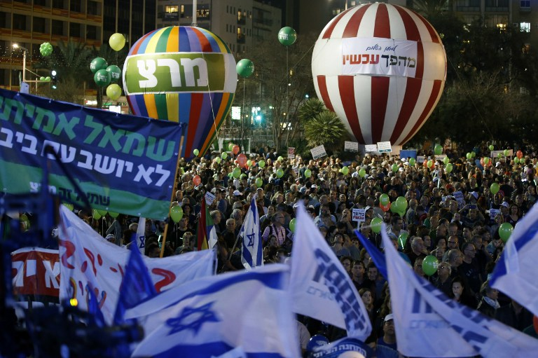 Israelis take part in a rally to ask for a change in the Israeli policy on March 7, 2015 on Rabin Square in Tel Aviv. Israelis go to the polls on March 17, in a vote that looks set to bring right wing Prime Minister Benjamin Netanyahu a fourth term in office. (photo credit: AFP/JACK GUEZ)