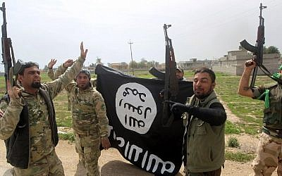 Members of the Iraqi paramilitary Popular Mobilization units celebrate with a flag of the Islamic State (IS) group after retaking the village of Albu Ajil, near the city of Tikrit, from the jihadist group, on March 9, 2015. (photo credit: AFP/Ahmad al-Rubaye)