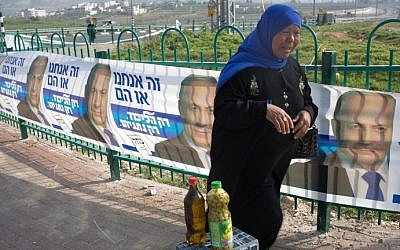 A Palestinian street vendor sells olive oil in front of campaign posters for Benjamin Netanyahu's Likud party on March 10, 201, in Givat Zeev, a West Bank settlement north of Jerusalem. (AFP/MENAHEM KAHANA)