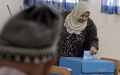 An Arab Israeli woman casts her vote at a polling station in the coastal city of Haifa, on March 17, 2015. (photo credit: AFP/AHMAD GHARABLI)