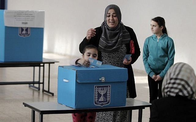 An Arab Israeli girl casts her mother's ballot at a polling station in the northern Israeli town of Umm al-Fahm on March 17, 2015. (photo credit: AFP / AHMAD GHARABLI)