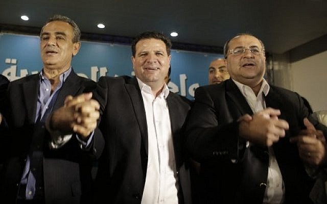 Arab Joint list candidates (from L-R) MK Jamal Zahalka, Joint List leader Ayman Odeh, and MK Ahmad Tibi raise their hands at the party's headquarters in the city of Nazareth, March 17, 2015, as they react to exit polls. (AFP/Ahmad Gharabli)
