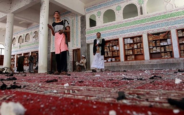 Yemeni armed men inspect the damage following a bomb explosion at the Badr mosque in southern Sanaa on March 20, 2015. (Photo credit: AFP/ MOHAMMED HUWAIS)
