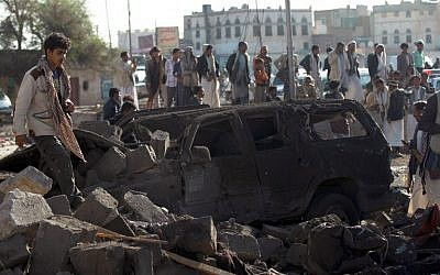 Yemenis stand at the site of a Saudi airstrike against Houthi rebels near Sanaa Airport on March 26, 2015, which killed at least 13 people. (photo credit: AFP/Mohammed Huwais)