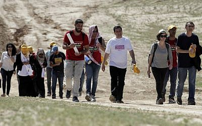 Joint List head Ayman Odeh, in white shirt, and Israeli left-wing MP Dov Khenin, on right, march alongside several dozen protesters in the Bedouin village of Wadi al-Naam on March 26, 2015. (AFP/AHMAD GHARABLI)